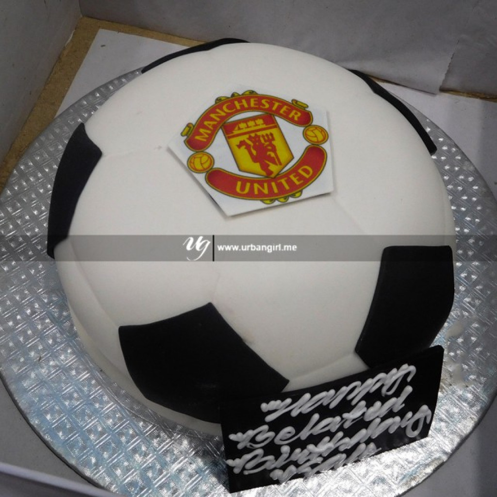 football shaped cake with manchester united logo on top football shaped cake with manchester